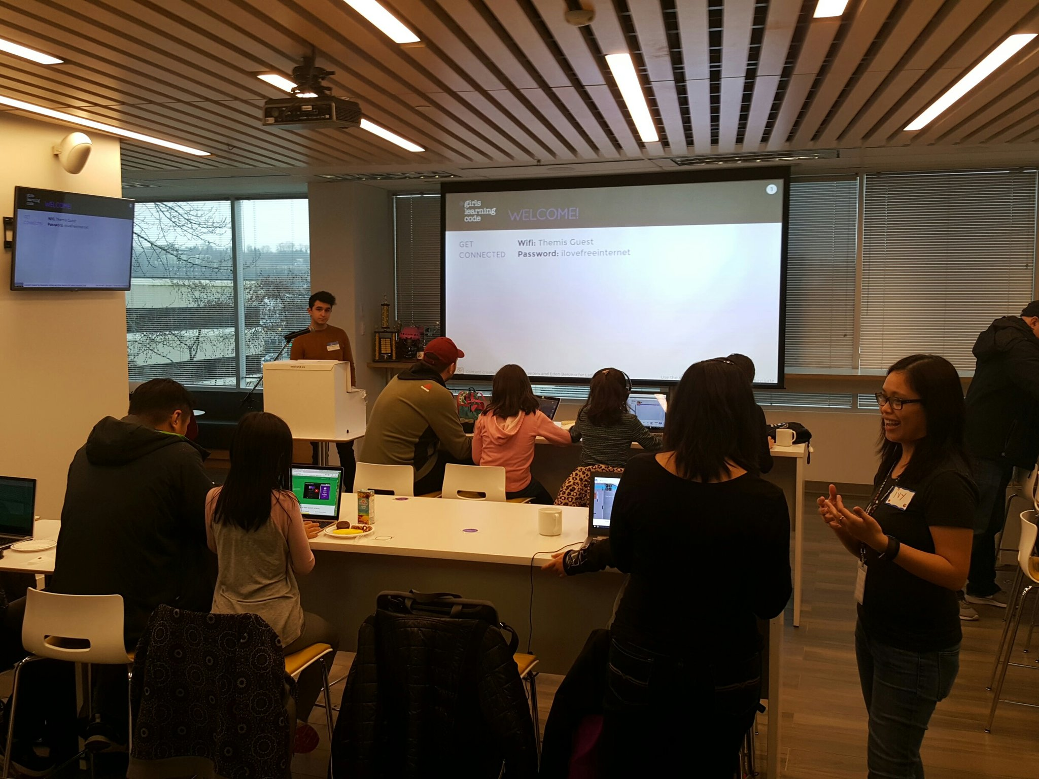 A group of girls and parents sit at laptops in front of a projector screen learning HTML/CSS.